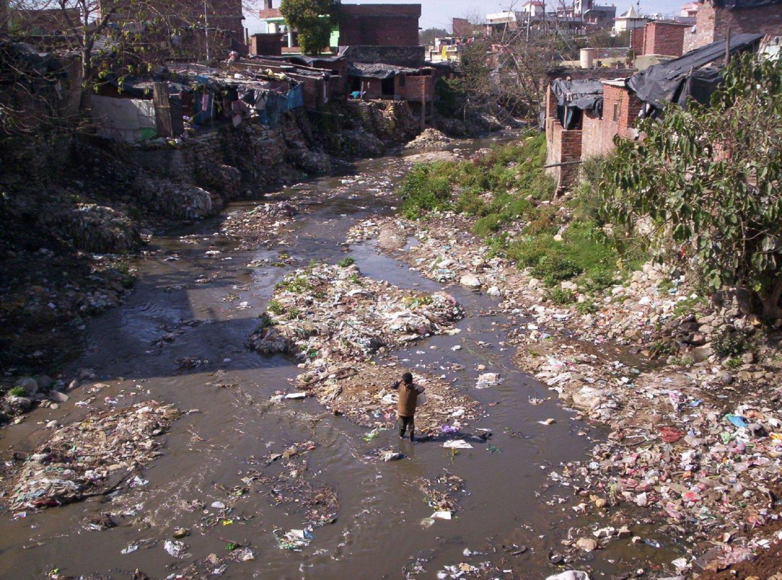 Un riu ple de deixalles transcorre pel mig d'un barri de barraques a l'Índia