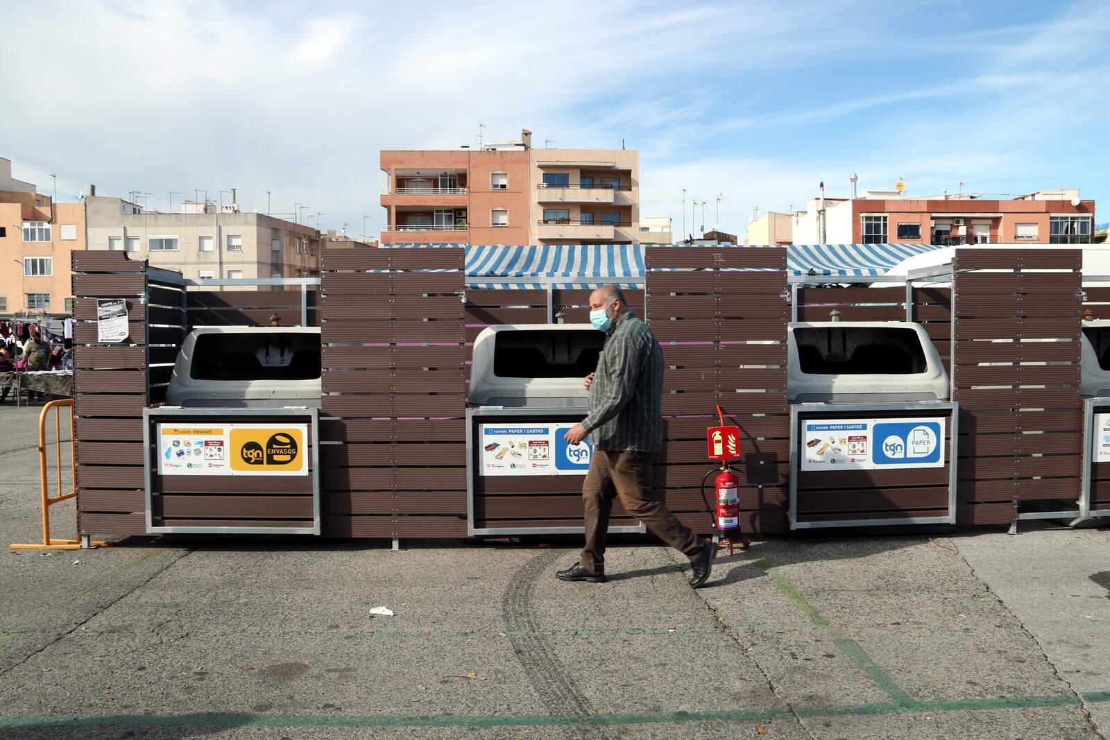 Home caminant davant els contenidros de recollida selectiva del mercat de Bonavista de Tarragona