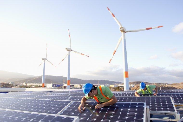 Instal·lació de plaques solars. Al fons, turbines eòliques.  | Departament de Territori i Sostenibilitat