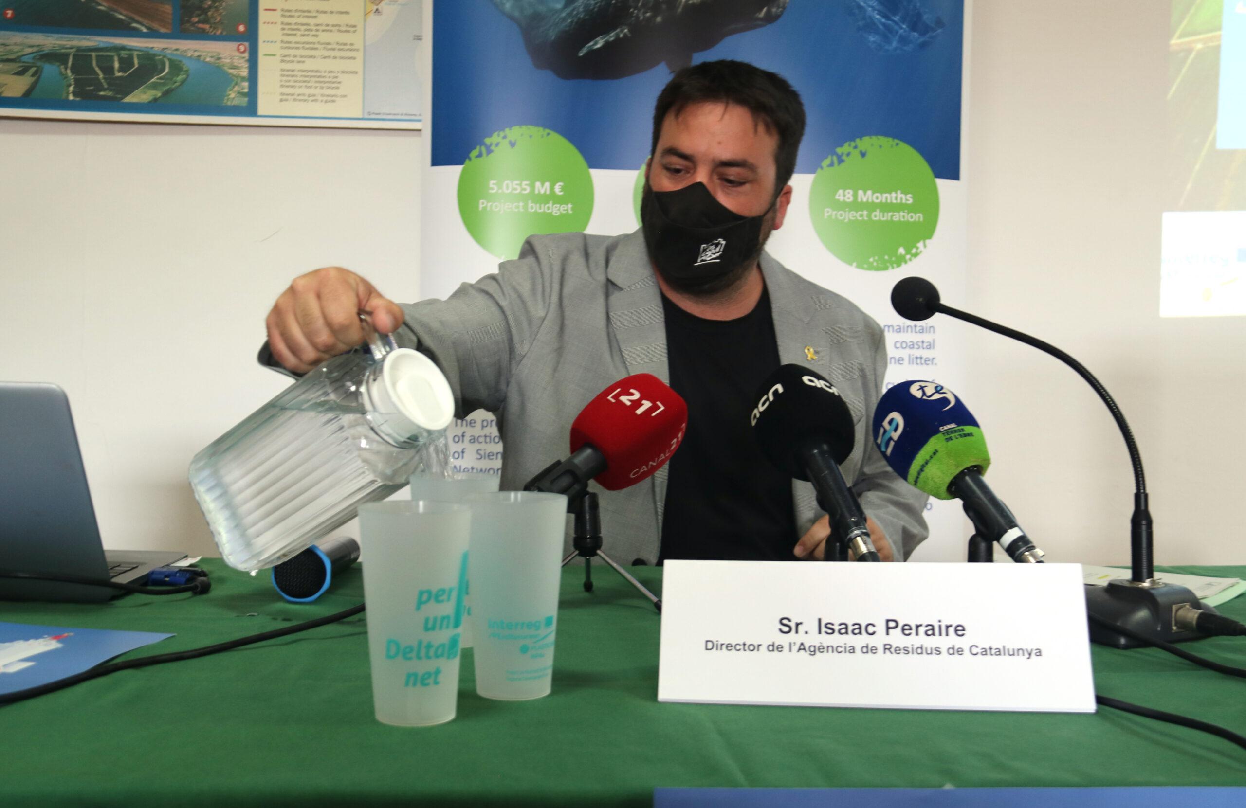 El director de l'Agència de Residus de Catalunya, Isaac Peraire, posant aigua en un dels gots reutilitzables que s'oferiran  a les guinguetes del Parc Natural del Delta de l'Ebre | ACN